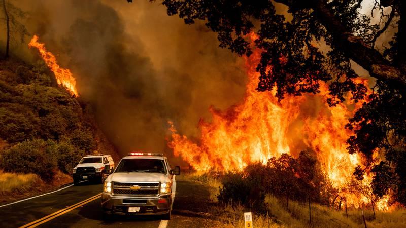 Bildet viser to biler og en stor brann i bakgrunnen.