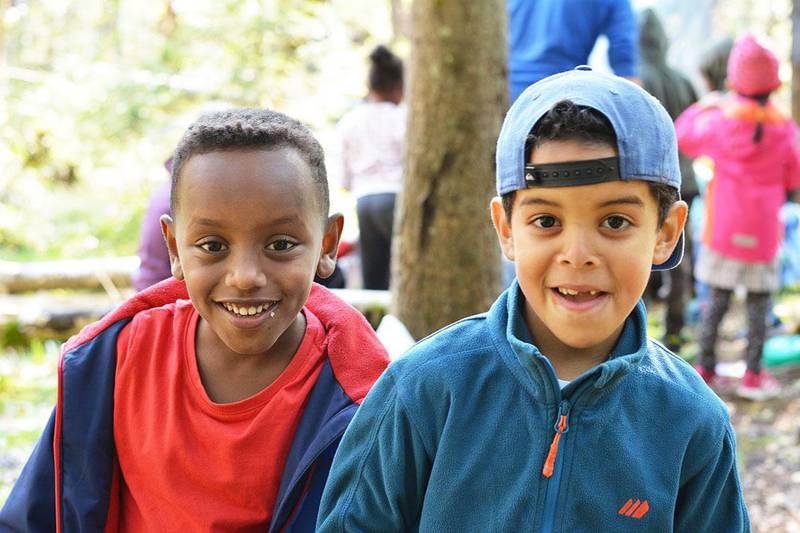 Bildet viser elevene Jaasiel og Mohamed som smiler. De trives med skole ute i det fri.