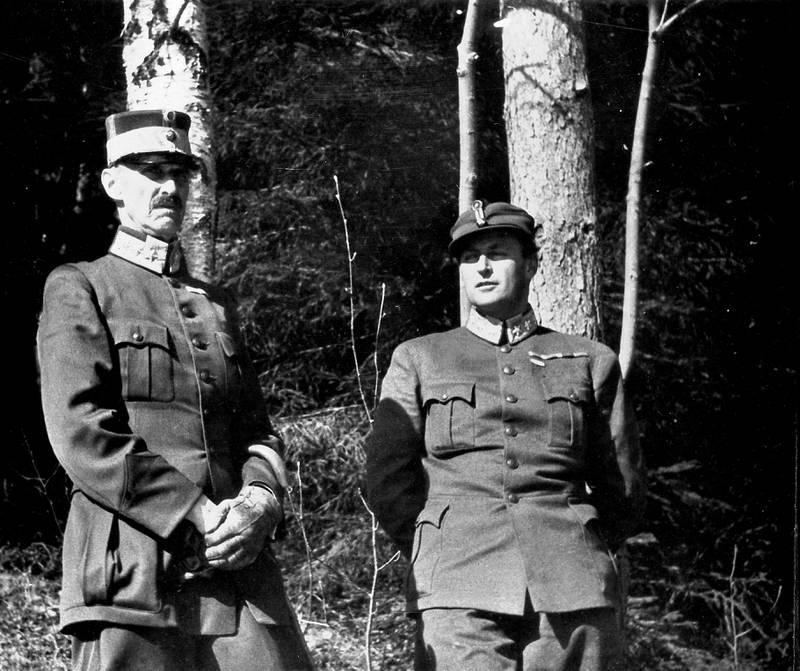 Bildet er av Kong Haakon og kronprins Olav (til høyre). Bildet er tatt foran noen trær. Begge har på militære uniformer. Bildet er i sort/hvitt.