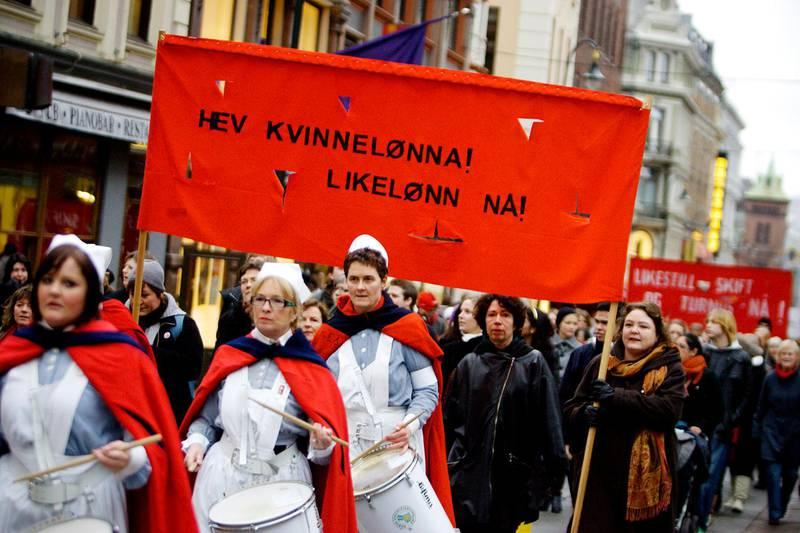 OSLO 20080308: Kvinnedagen l¯rdag 8. mars ble bl.a. markert med et demonstrasjonstog gjennom Oslos gater. Plakat / banner : Hev Kvinnel¯nna ! Likel¯nn N!Sykepleiere i uniform og r¯de kapper , spiller ptrommer.Foto: Kyrre Lien / NTB  .