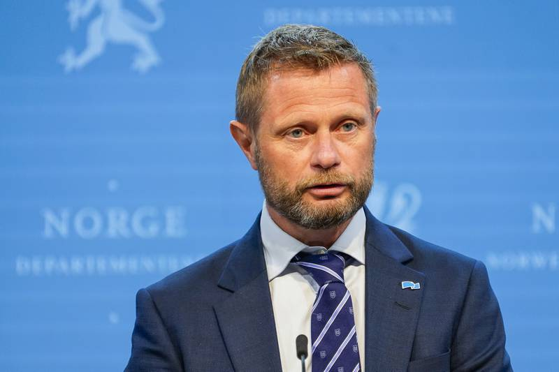 Bildet er av helseminister Bent Høie. Han har på seg skjorte og dress, og står foran en blå vegg. Han har kort hår og skjegg. Foto: Torstein Bøe / NTB