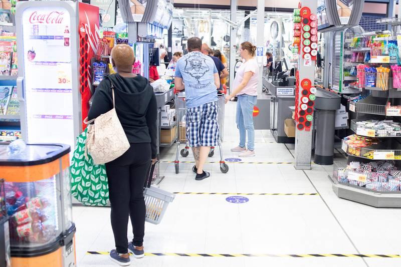 Bildet er av folk som står i kø på en svensk matbutikk. Det er merker på gulvet som viser hvor tett folk kan stå hverandre i køa.