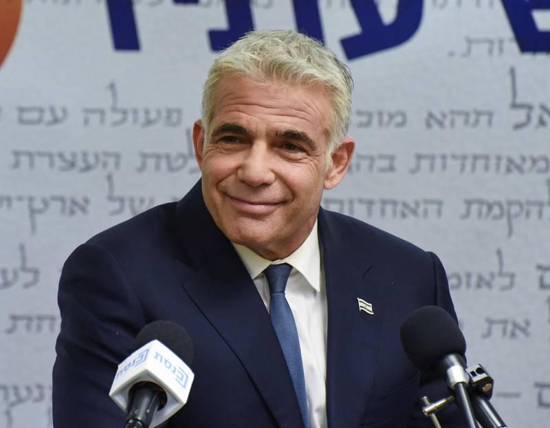 Bildet er av Yair Lapid. Han har på dress og sitter bak mikrofoner. Han har grått hår og mørke øyenbryn. Han smiler.