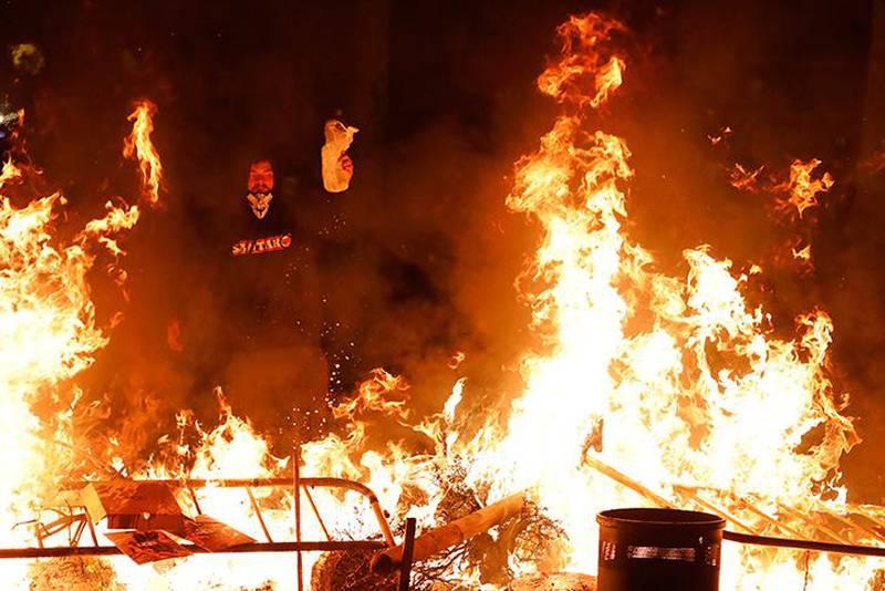 Bildet viser en person med maske som kaster brennbart materiale på en barrikade i full fyr. For fjerde dag på rad var det store demonstrasjoner i Barcelona.