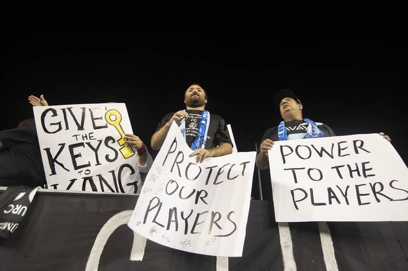 Bildet er av supportere som protesterer på en fotballkamp. De har skilt med krav om at spillere må få bedre beskyttelse og mer makt.