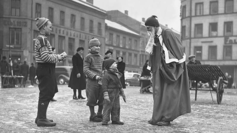 Bildet viser julenissen som snakker med barn på gata i Oslo i 1954.