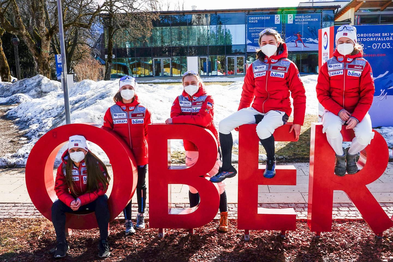 Bildet er av fem jenter i røde jakker. De sitter og lener seg på og i bokstavene O, B, E og R. De er skåret ut. Bildet er tatt i Oberstdorf i Tyskland. De har på munnbind.