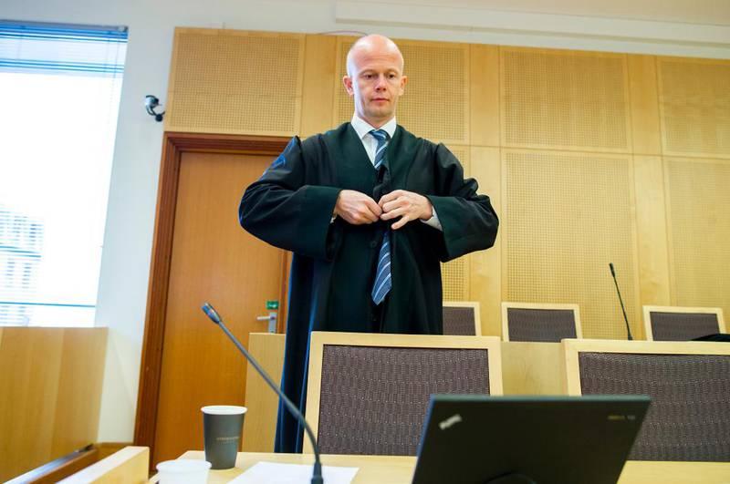 Bildet viser advokat Svein Holden som knepper på seg kappen sin. Han står i en rettssal.