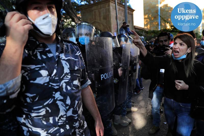Bildet er av en ung kvinne som demonstrerer. Hun roper til en av flere politimenn som står på rekke med opprørs-utstyr.  Politimannen snakker i telefon og ser bort fra henne. Det er logo for ukens oppgave oppe i det høyre hjørnet.