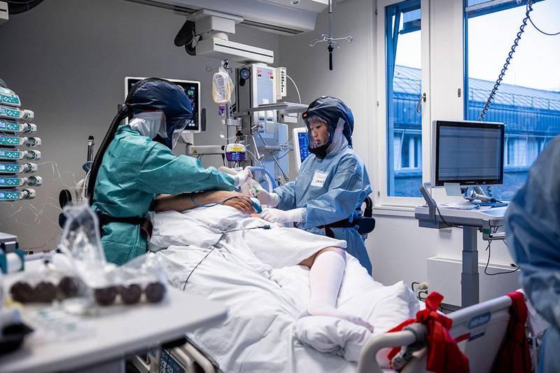 Bildet viser en pasient som får behandling for korona av to ansatte ved Rikshospitalet i Oslo.