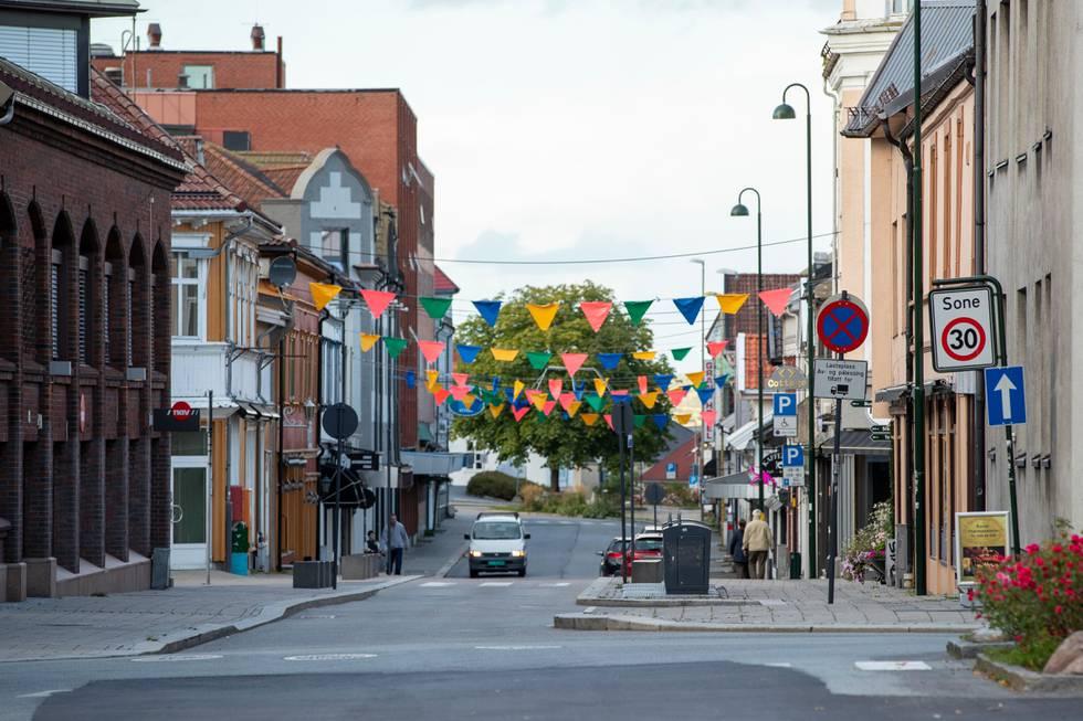 Bildet er fra sentrum av Sarpsborg by. Det henger vimpler høyt over gaten. Men det er nesten tomme gater. Bildet er fra flere hundre personer ble satt i karantene i byen tidligere i år.