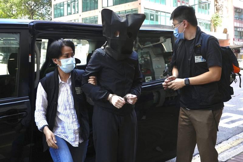Bildet er av en mann som følges av politiet etter å ha blitt pågrepet. Han har en hette over hodet. Foto: Vincent Yu / AP / NTB