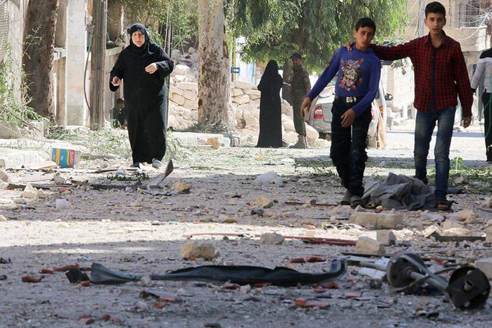 Bildet viser en gammel kvinne og to unge gutter på gata i Aleppo. Rundt dem ligger restene av ødelagte bygninger.
