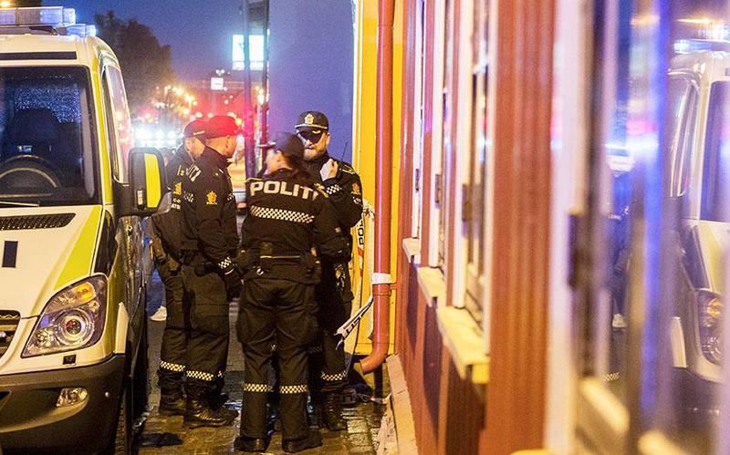 Bildet viser politifolk utenfor leiligheten hvor to personer ble drept i Trondheim sentrum forrige mandag. Nå blir den siktede avhørt.