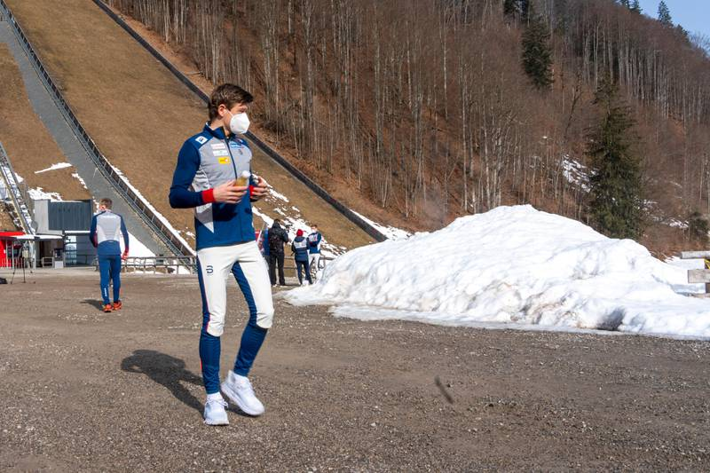 Bildet er av skiløperen Johannes Høsflot Klæbo. Han går i treningstøy og munnbind. Det er grus der han går. I bakgrunnen er det en hoppbakke uten snø. Det ligger en liten haug med snø på siden av ham.