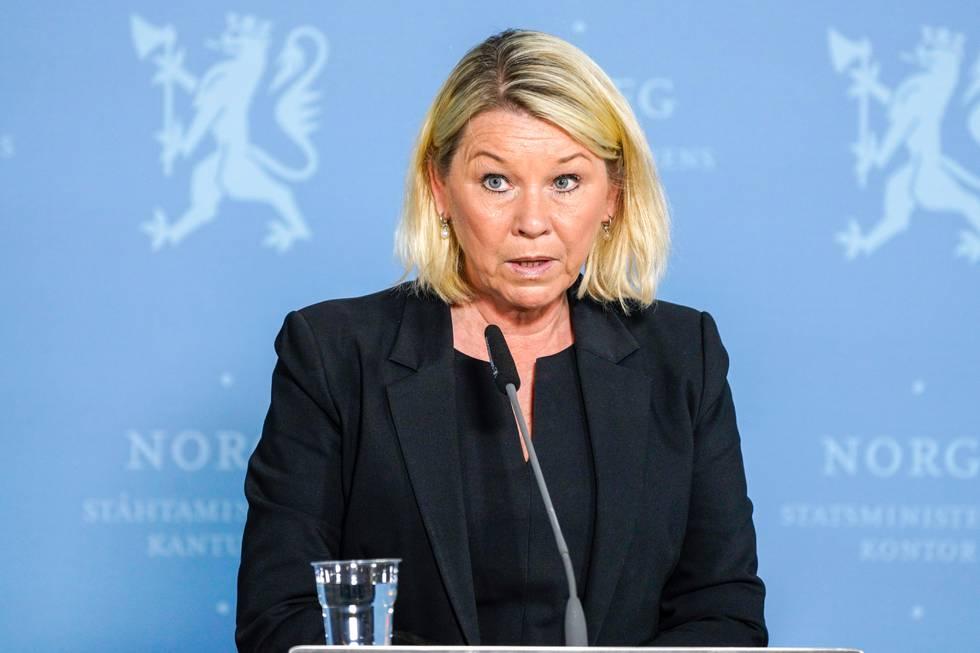 Bildet er av justisminister Monica Mæland. Hun står foran en blå vegg med riksløven på. Hun har en mikrofon foran seg.