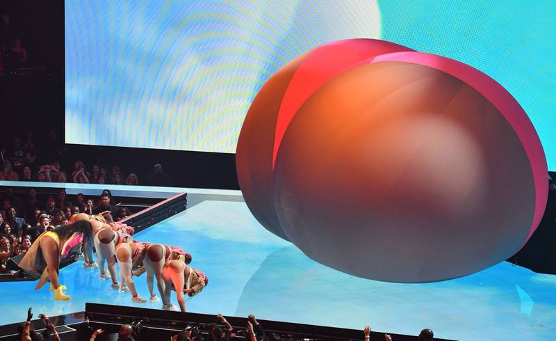 Bildet viser artisten Lizzo på scenen. Hun er sammen med dansere og en stor ballong som ligner en rumpe.