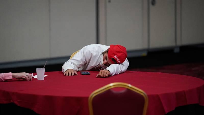 Bildet viser en Trump-tilhenger som hviler over et bord.