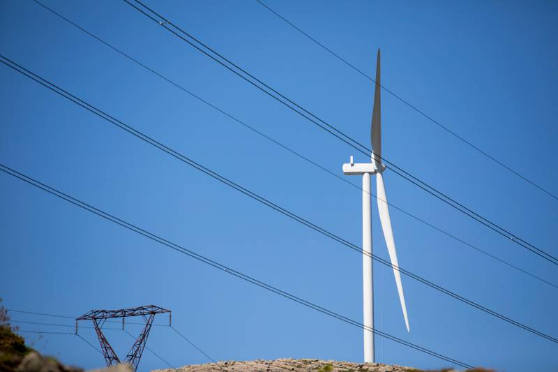 Bildet er av en vindmølle. Den er omgitt av høyspentmaster med strømkabler.