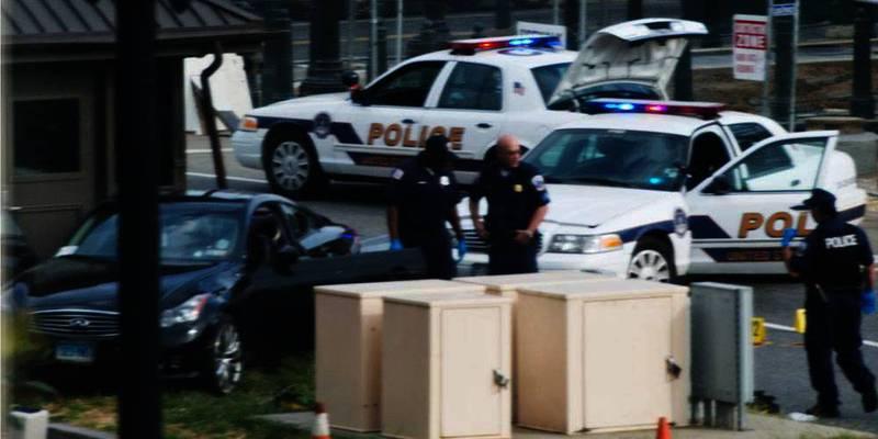 Bildet viser politibiler og en svart bil som står på skrå ved en gressplen. En kvinne kjørte i vill fart fra Det hvite hus mot Kongressen i USA. Hun ble skutt av politiet.