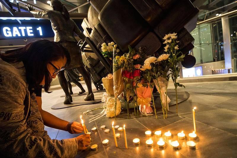 Bildet viser folk som tenner lys ved kjøpesenteret der flere ble drept lørdag.