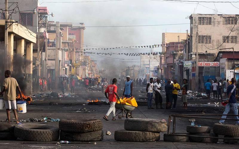 Bildet viser en gate i Port-au-prince i Haiti. Folk står bak en stengsel laget av bildekk. Folk krever at presidenten slutter.