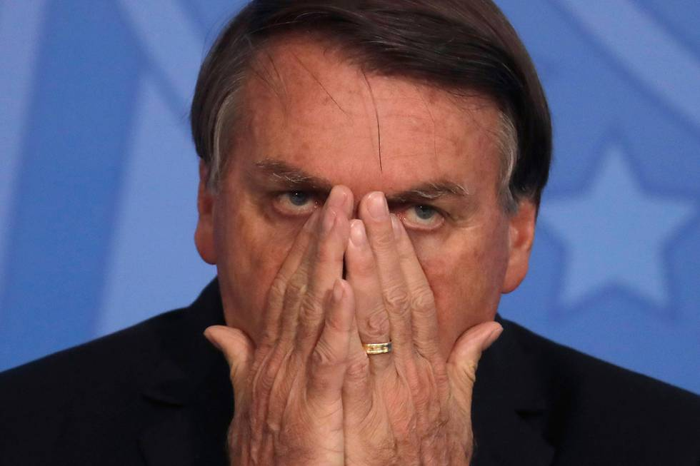 Bildet er av Brasils president Jair Bolsonaro. Han holder hendene over munn og nese.