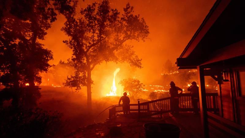 Bildet viser brannfolk som ser en brann nærme seg.