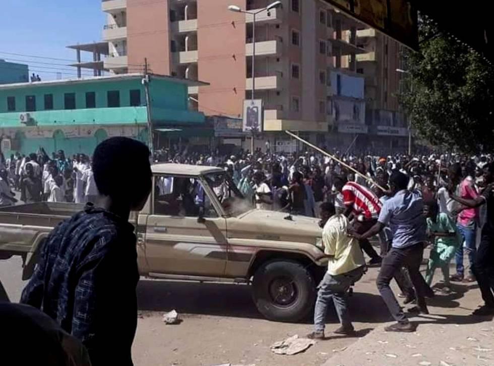 Bildet viser folk i Sudan som protesterer og angriper en bil.