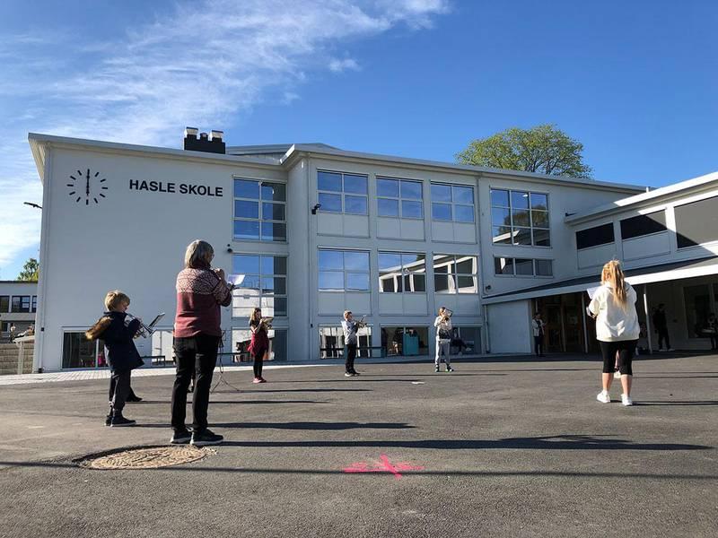 Bildet viser Mellombrassen til Hasle Skolekorps som øver til 17. mai. Endelig kan de spille sammen igjen, men ute og med avstand.