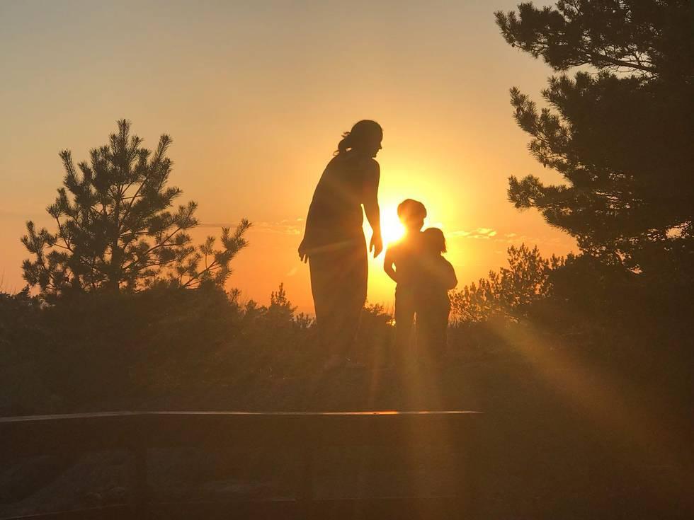 Bildet viser tre personer i solnedgang. Fredag kan det komme nye varme-rekorder. Det er meldt veldig varmt vær i store deler av landet.