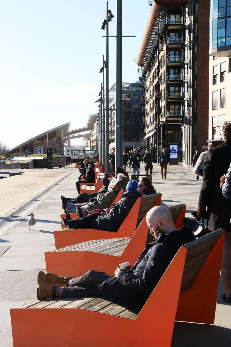 Bildet viser folk som soler seg på benkene på Aker Brygge i Oslo.