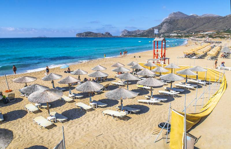 Bildet er av parasoller og solsenger på en strand. Det er blått hav. Bildet er fra Falasserna på Kreta i Hellas. Foto: Halvard Alvik / NTB