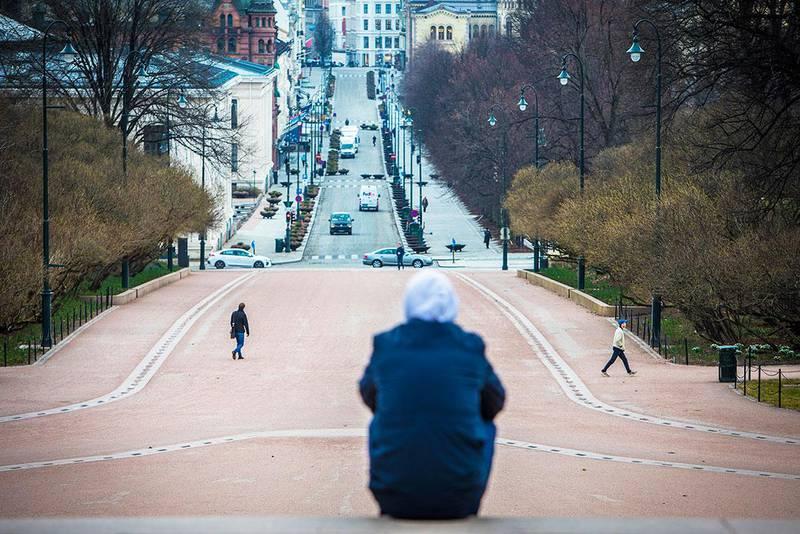 Bildet viser en person som sitter på toppen av Karl Johans gate i Oslo. Det er lite folk i byen. Mange jobber fra hjemmene sine som følge av korona-viruset. Det gjør at det er færre som reiser inn til Oslo og andre store byer.