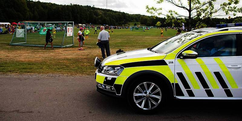 Bildet viser en politibil ved en fotballbane. Tidligere i uka passet politifolk på fotball-spillerne på turneringen Norway Cup. Det blir nå slutt på ekstra politi på steder med mye folk. Politiet mener det ikke lenger er så høy fare for et terror-angrep.