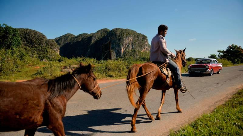 Bildet viser en mann på en hest på Cuba. Han leier en annen hest i tillegg.