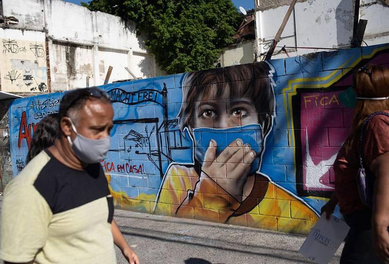 Bildet viser en mann og en dame som går forbi et veggmaleri av en gutt med munnbind i Brasil. Brasil håndterte korona-viruset dårligst i verden. Det viser en studie.