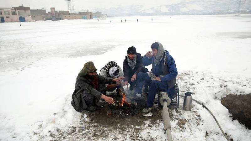 Bildet viser folk som varmer seg på bål utenfor Kabul.