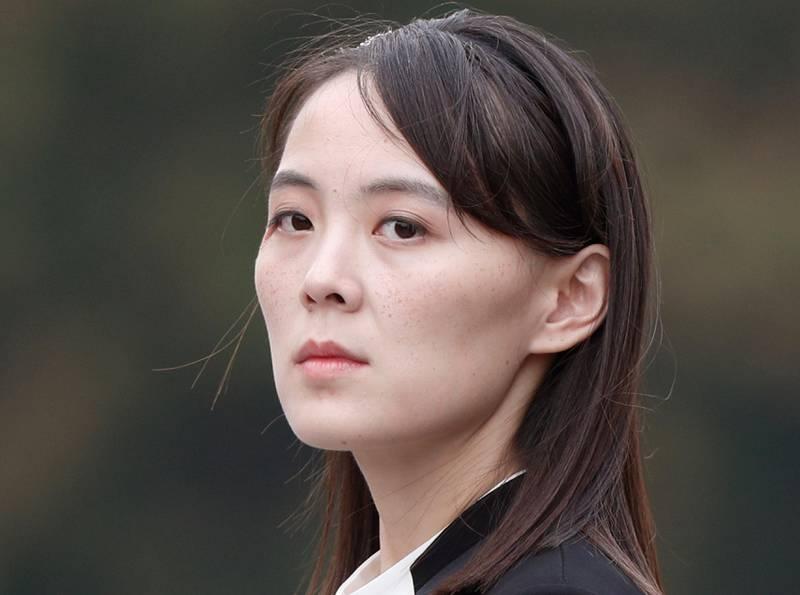 Bildet er av Kim Yo-jong.  Hun ser på skrå over skulderen og inn i kameraet. Hun har hvit skjorte og svart jakke. Hun er lys i huden og har glatt mørkt hår.
