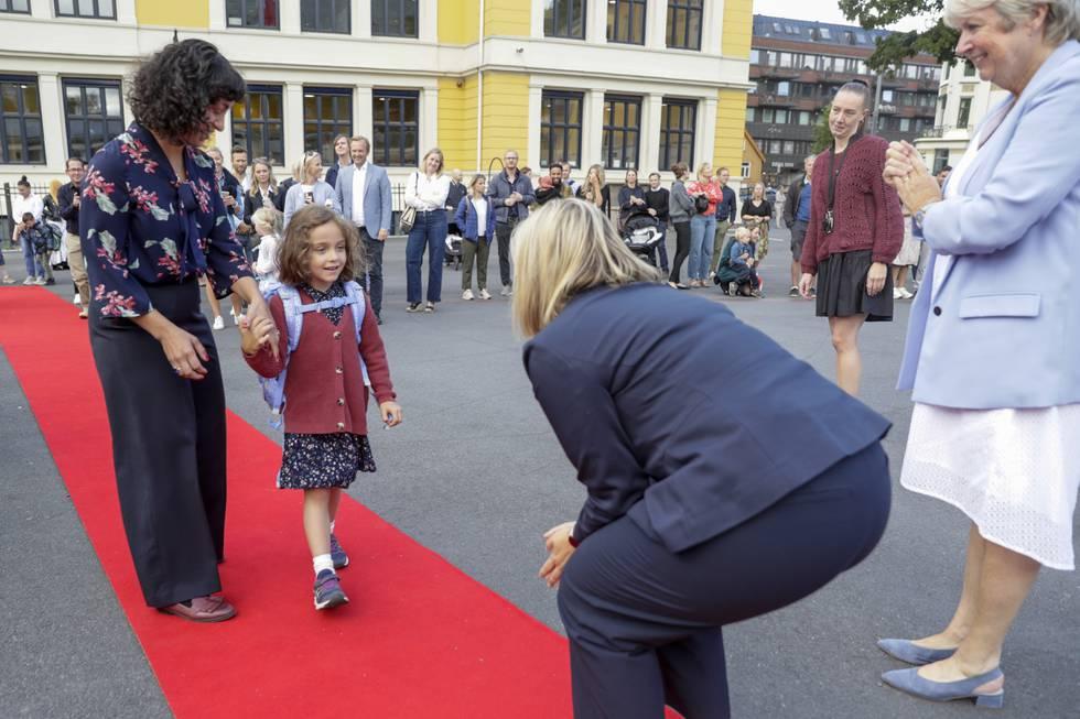 Kunnskaps- og integreringsminister Guri Melby (V) tar imot 6 år gamle Olivia Motland som sammen med sin mor, Natasha Meland, ankommer til første skoledag på Uranienborg skole mandag. Foto: Berit Roald / NTB