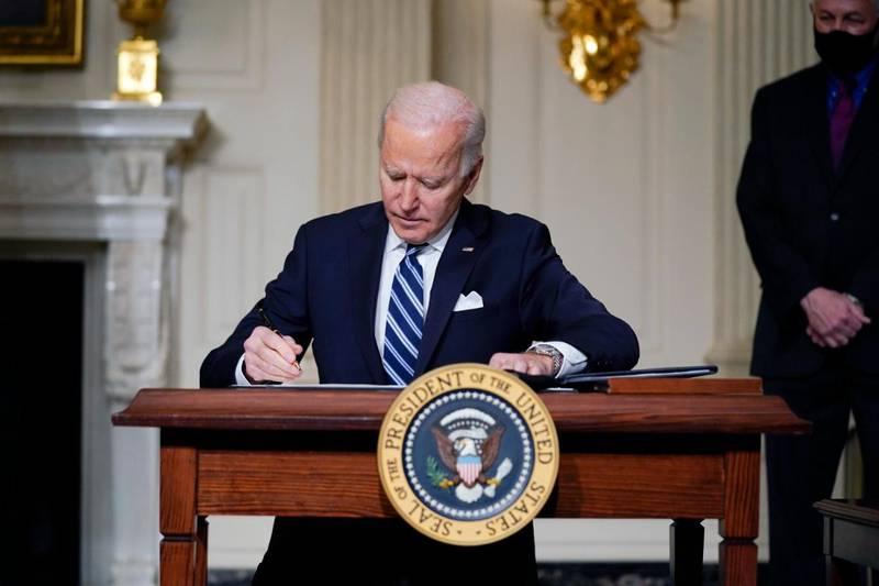 Bildet er av president Joe Biden. Han sitter bak en pult og skriver under på en presidentordre om klima.