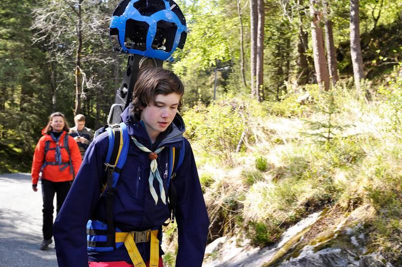 Bildet viser en speider med et stort kamera på ryggen som stikker opp fra en sekk.
