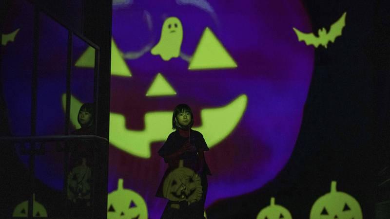 Bildet viser et barn og mange lysende spøkelser og gresskar. Bildet er fra halloween-feiring i Japan.