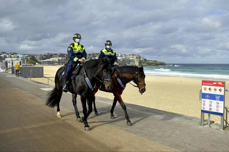 Politi på hester ved Bondi Beach passer på at ingen bryter koronanedstengingen. Foto: Joel Carrett / AAP Image via AP / NTB