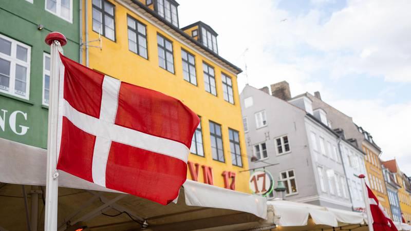 Bildet viser Nyhavn i København i Danmark. Det danske flagget er i framgrunnen.