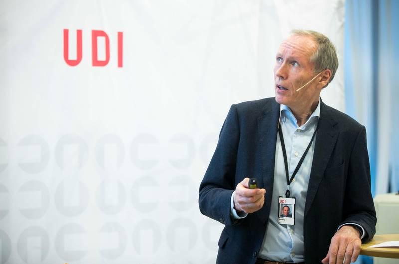 Bildet er av UDI-direktør Frode Forfang. Han står foran en skjerm. Der er logoen til UDI.
