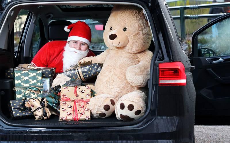 Bildet er av en nisse i bagasjerommet på en bil. Han er gjemt bak gaver og en stor bamse.