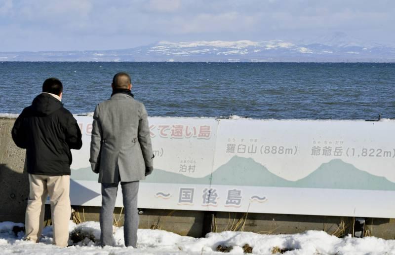 Bildet viser to menn som ser mot en øy.