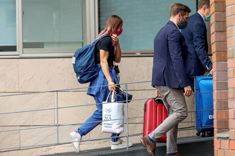 Bildet er av den hviterussiske sprinteren Krsystsina Tsimanouskaya. Hun bærer et tøynett med OL-merke på i en hånd og har en sekk på ryggen. Hun går inn i bygningen i Tokyo der den polske ambassaden holder til.