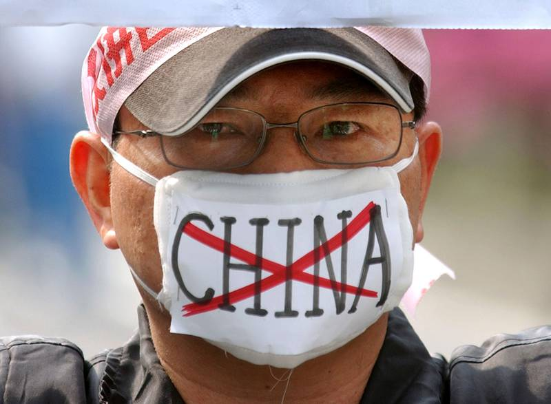 Bildet viser en mann med ansiktsmaske. Den har ordet Kina med en strek på.
